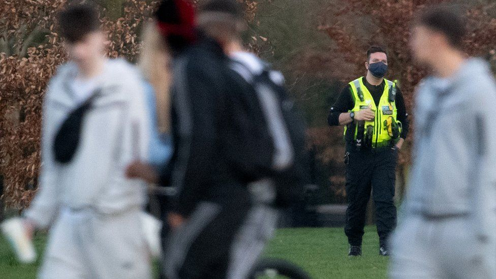 A police officer in a park with a group of unidentifiable men in the foreground