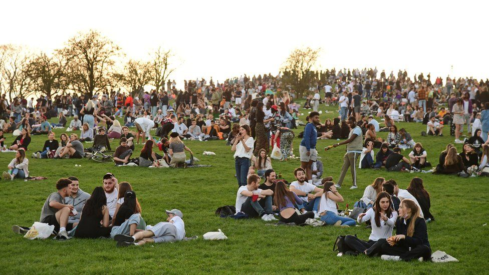 People enjoy the evening sunlight on Primrose Hill, north London, on Tuesday