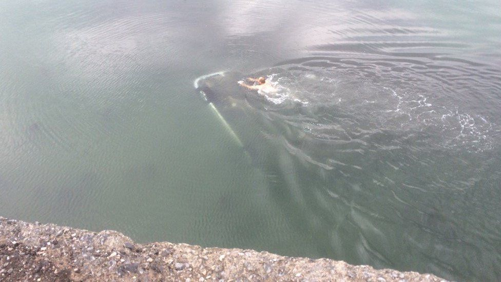 Man swimming to overturned car
