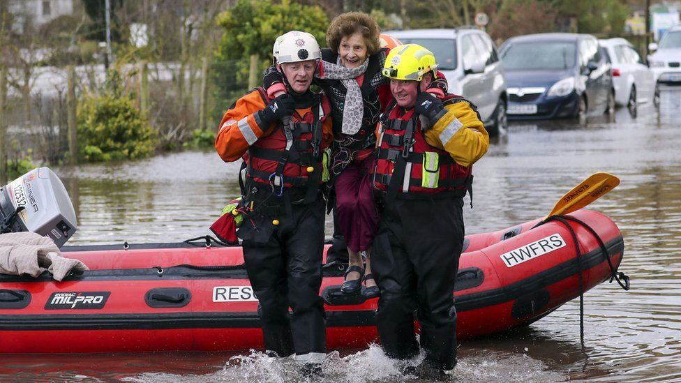 Rescue workers lifted a woman to safety in the village of Whitchurch
