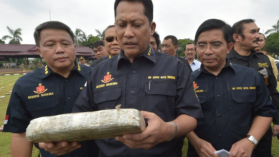 Budi Waseso (C), Indonesian chief of criminal investigation division, holds a seized marijuana block at the national police headquarters in Jakarta on May 11, 2015.