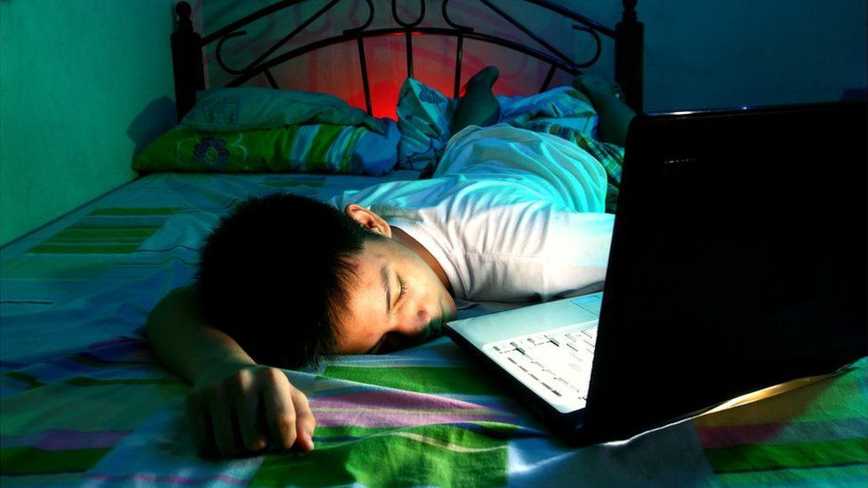 A child with a computer in bed
