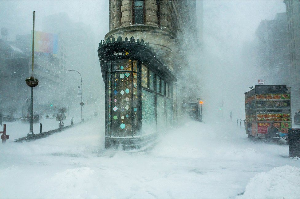 Snow covers the street and blows across this New York street scene
