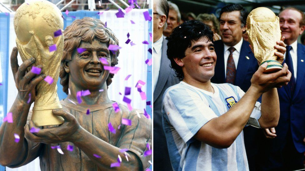 A statue of Diego Maradona holding the World Cup beside a photo of the image on which it was based