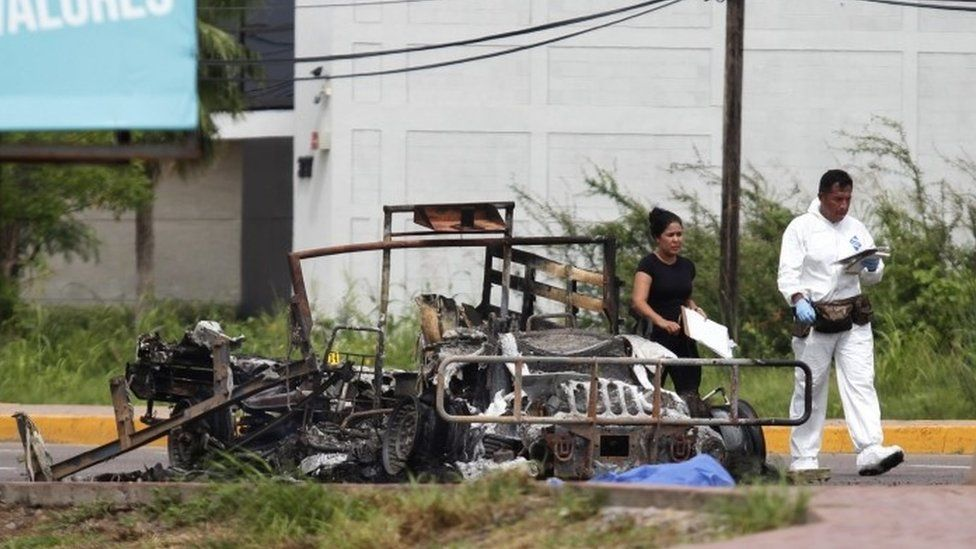 Forensic experts stand next to a burned vehicles after an ambush perpetrated by alleged members of an organized crime syndicate in Culiacan, Sinaloa, Mexico (30 September 2016)