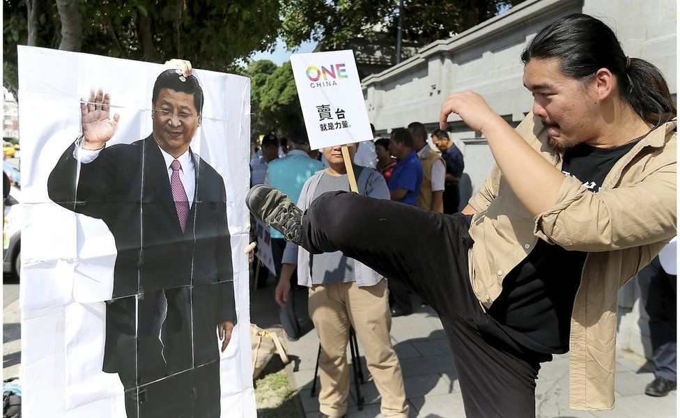 An activist kicks a portrait of Chinese President Xi Jinping during a protest against the upcoming meeting between Taiwan's President Ma Ying-jeou and Chinese President Xi Jinping, in front of the Presidential Office in Taipei, Taiwan, 5 November 2015.