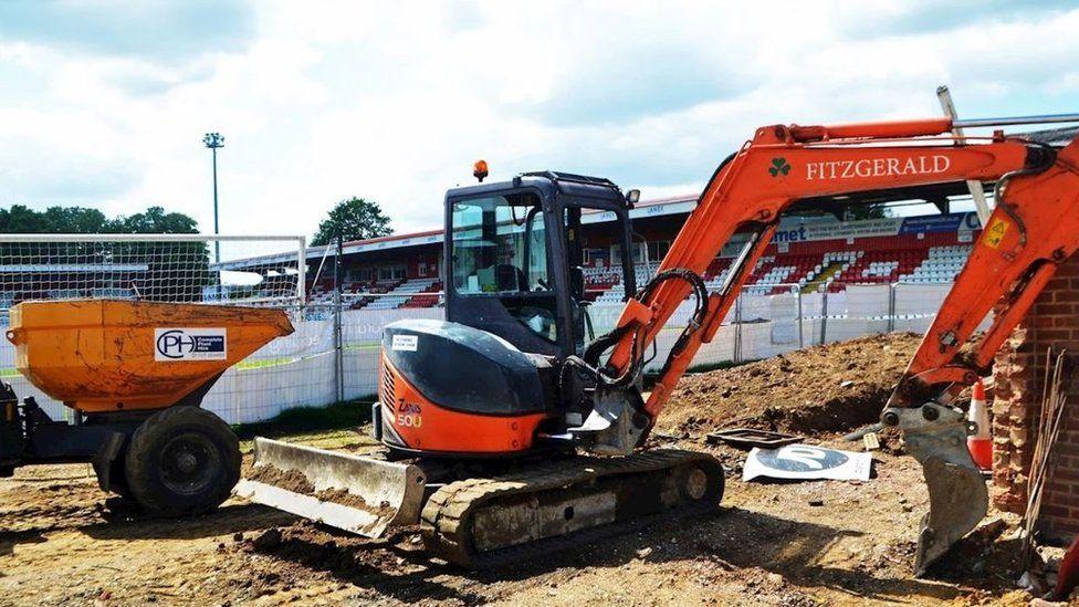 Digger at football ground