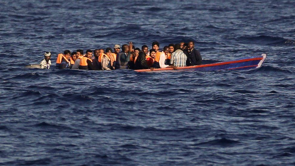 Migrants and refugees fleeing Libya aboard a wooden boat in the Mediterranean sea on 28 August 2016