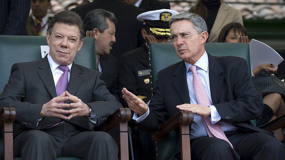 Juan Manuel Santos and Alvaro Uribe at a military event.