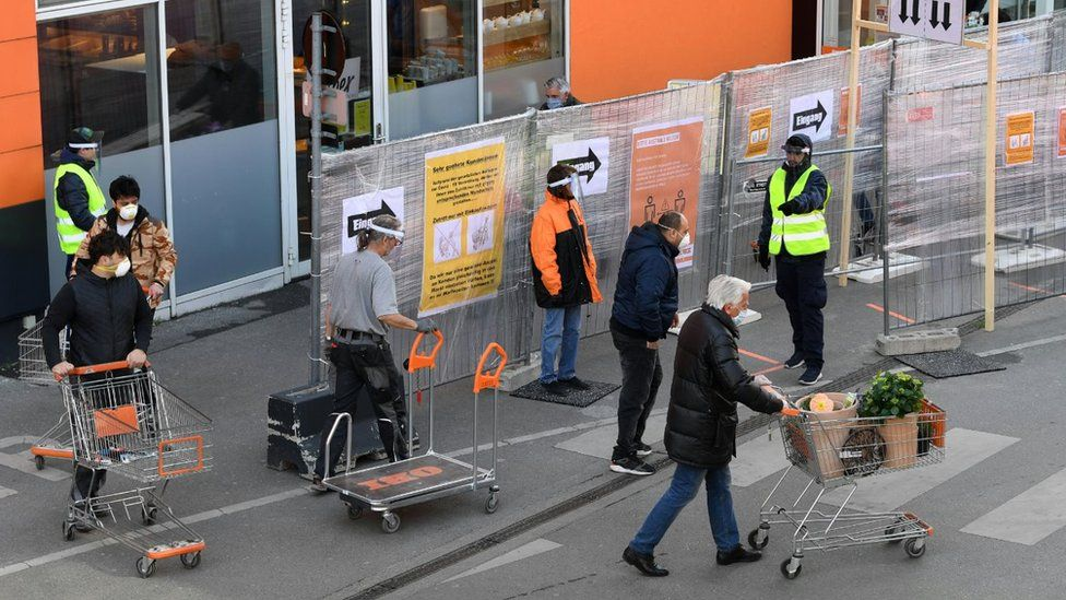 Customers wearing face masks push shopping carts in front of a DIY store in Vienna on 14 April