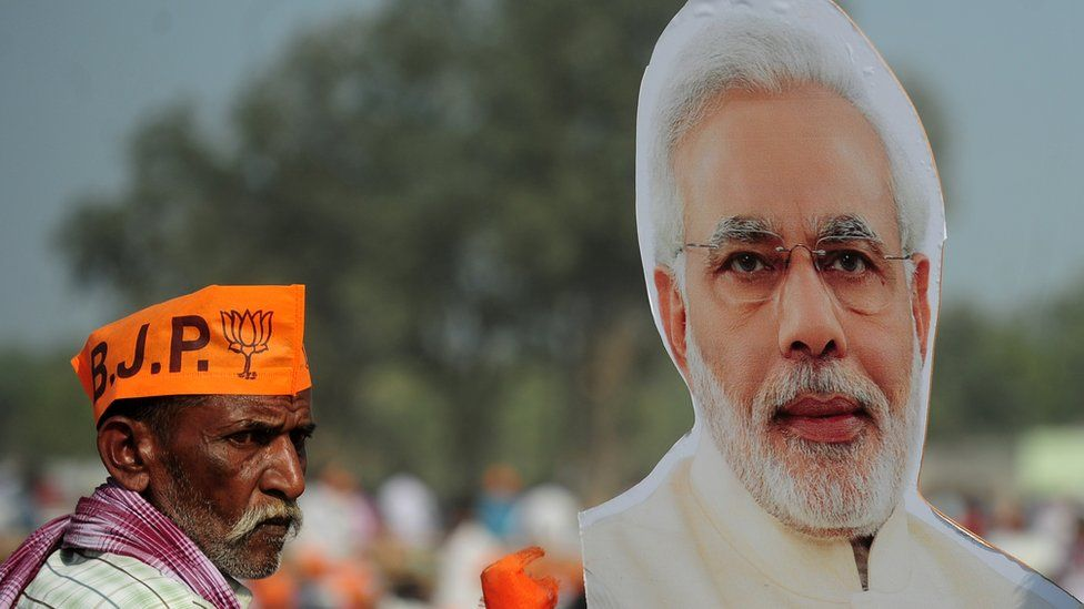 Supporters of India's Bharatiya Janata Party (BJP) listen to BJP Leader and Indian Prime Minister Narendra Modi as he speaks during a state assembly election rally in the village of Andawa on the outskirts of Allahabad on February 20, 2017.
