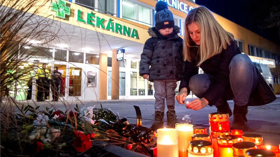 People light candles as they pay their respects for the victims of the shooting at a hospital in Ostrava, Czech Republic, 10 December 2019