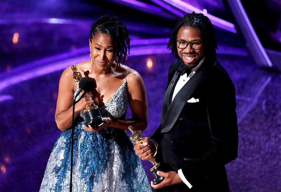 Karen Rupert Toliver and Matthew A. Cherry hold Oscars