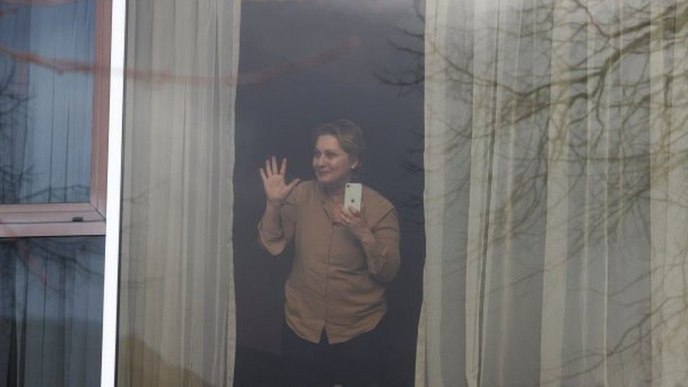 Zari Tadayon gestures from a window of the Radisson Blu Hotel at Heathrow Airport