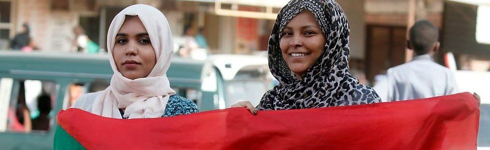 Two women hold a Sudanese flag as Sudanese protesters demonstrate in Khartoum