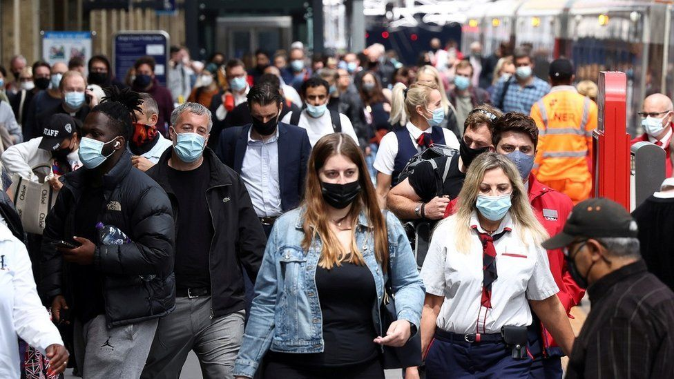 People wearing face masks walk at King's Cross Station