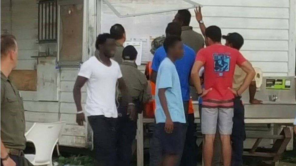 A supplied photo of refugees at Manus detention centre checking a notice board