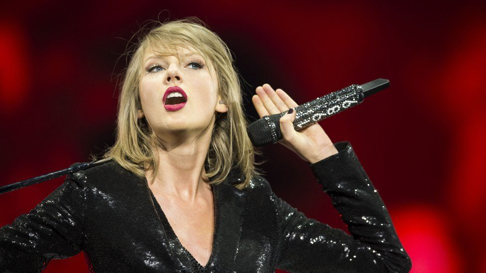 Taylor Swift holds microphone on-stage while performing