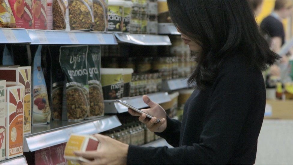 A woman checking her phone in a supermarket