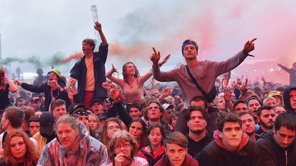 Festival-goers sitting on each others' shoulders in a crowd