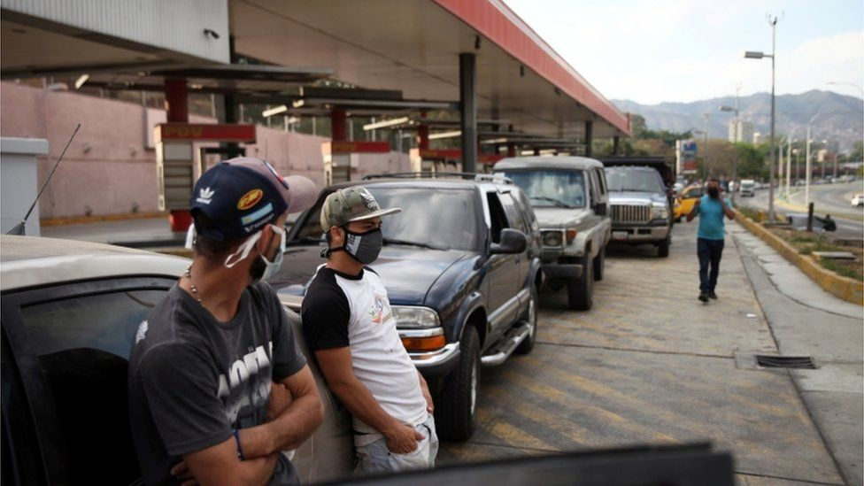 People wearing protective masks stand beside vehicles in line at a fuel station during the nationwide quarantine in response to the spread of coronavirus disease (COVID-19) in Caracas, Venezuela 30 March 2020
