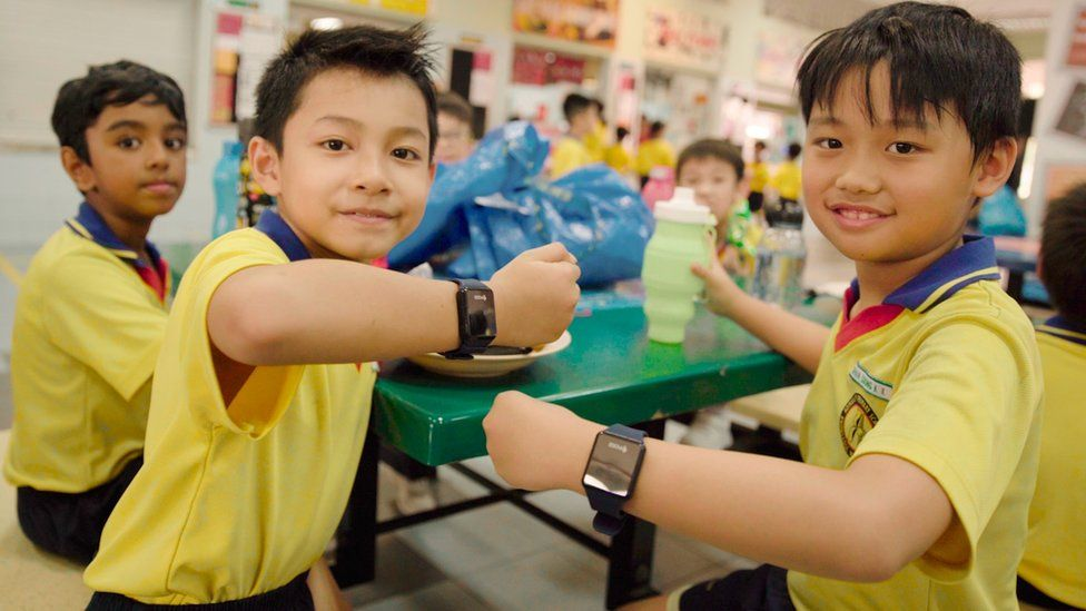 Children at Admiralty High School in Singapore show off their new payment wristbands