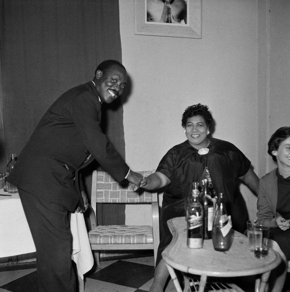 Roger DaSilva shakes hands with US jazz singer Velma Middleton in a self-timed photograph.