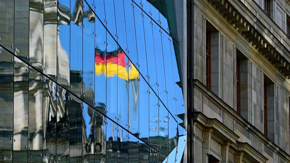 The Reichstag building, seat of the German lower house of Parliament, the Bundestag, is reflected in an glass facade in Berlin