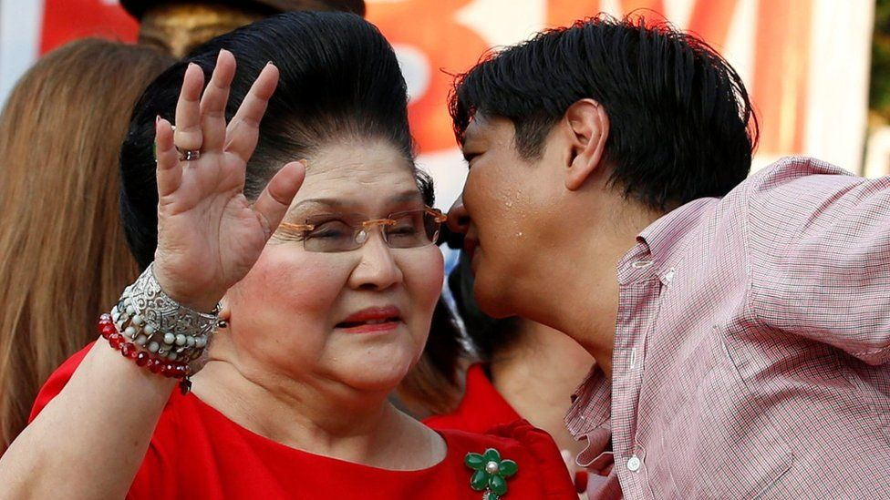 """Vice-presidential candidate """"BongBong"""" Marcos whispers to his mother, former First Lady and Congresswoman Imelda Marcos, at an event where he announced his candidacy, in Manila on 10 October"""