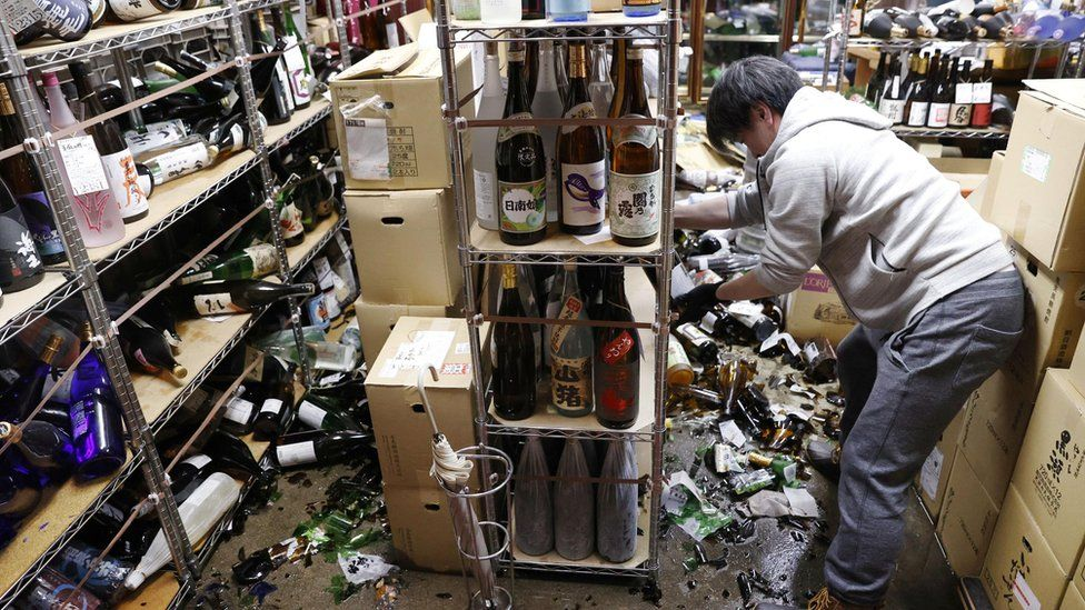 Store owner cleaning up smashed bottles in Fukushima liquor shop