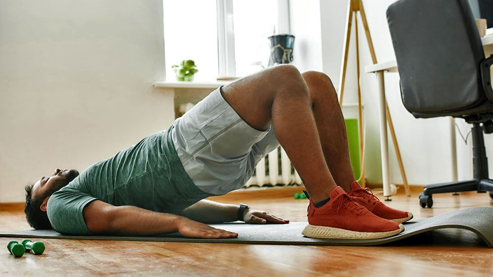 Stock image of man exercising at home