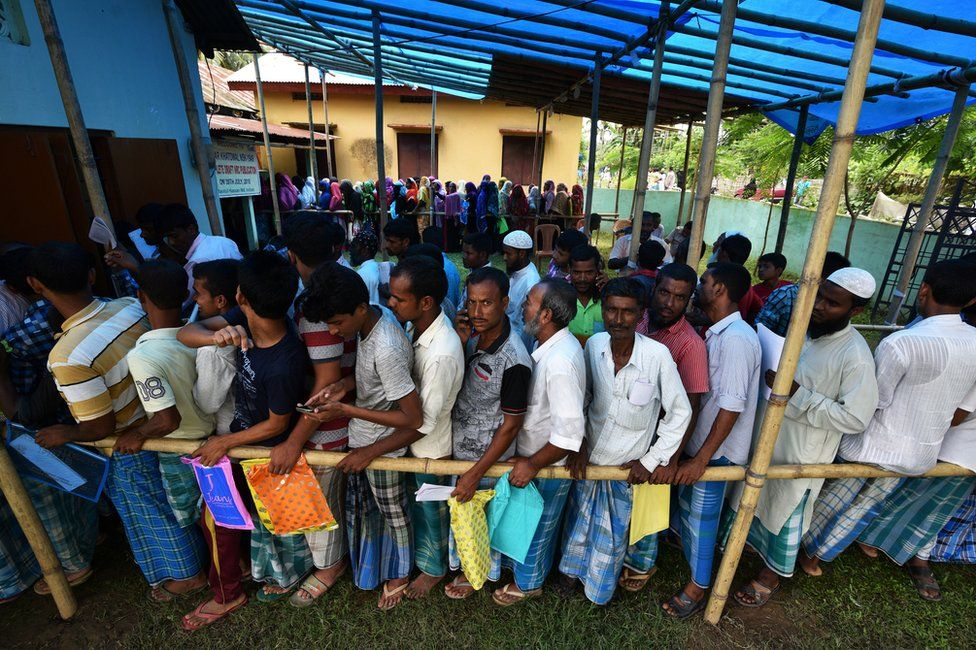 People wait in queue to check their names on the draft list at the National Register of Citizens centre at a village in Assam on 30 July 2018.