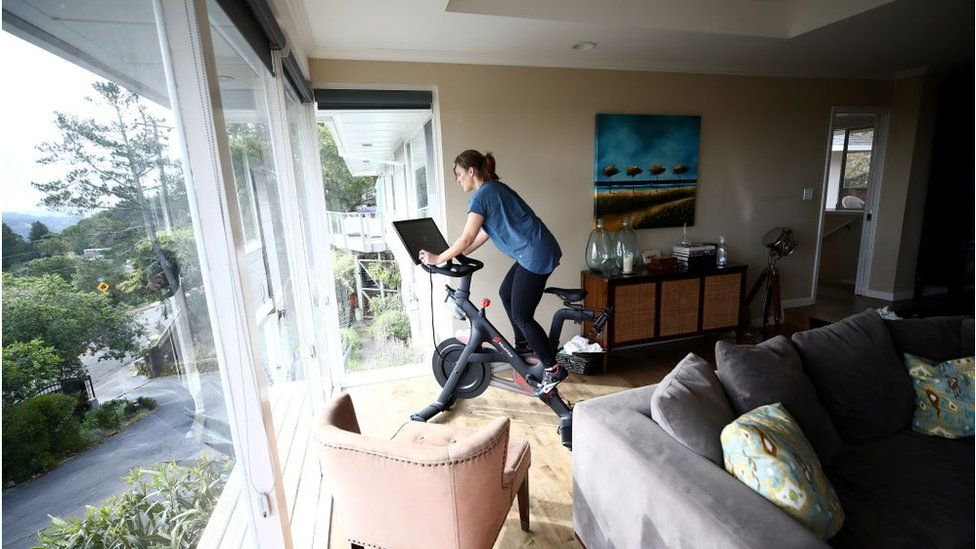 A woman riding a peloton bike at home in the living room
