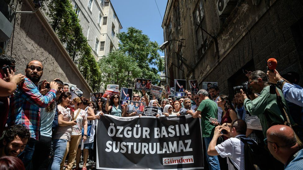 """Protesters hold pictures of jailed RWB activist Erol Onderoglu, journalist Ahmet Nesin and activist and academic Sebnem Korur Fincanci, with a banner reading """"free press will not be silenced"""", in front of the pro-Kurdish Ozgur Gundem newspaper's headquarters in Istanbul on 21 Jun 16"""