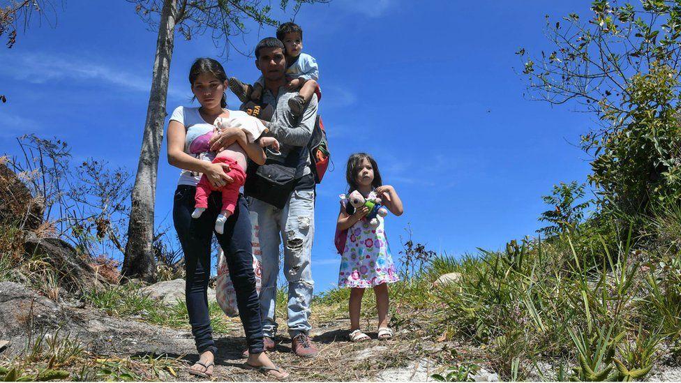 Venezuelan police officer Cesar Marcano (C) along with his wife Adriana Ballera (L) and their children Alexandra (R), Cesar Jesus (top) e Adranlleli seek refuge in Brazil, at the Brazil-Venezuela border, in Pacaraima, Roraima state, Brazil on February 25, 2019.