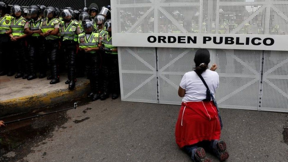 A woman kneels down front of riot police during Caracas protest 22 April 2017