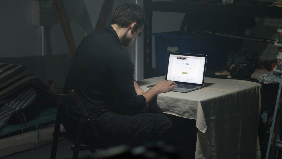 Man using laptop in darkened room