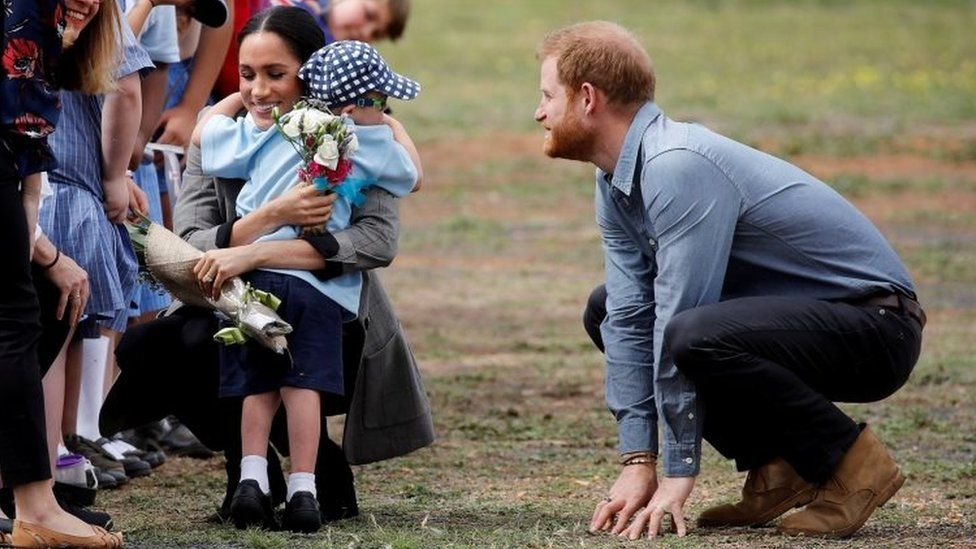 Prince Harry and Meghan, Duchess of Sussex, hug Luke Vincent, five, after arriving at Dubbo airport, Dubbo, Australia