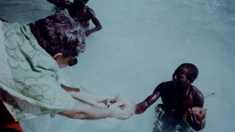 TN Pandit handing a coconut to a Sentinelese man