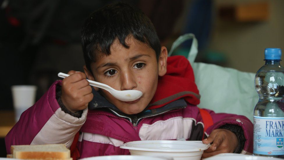 A young boy eats soup at a shelter for migrants who had arrived on buses chartered by Austrian authorities and will likely continue towards the nearby border to Germany on October 17, 2015 in Kollerschlag, Austria