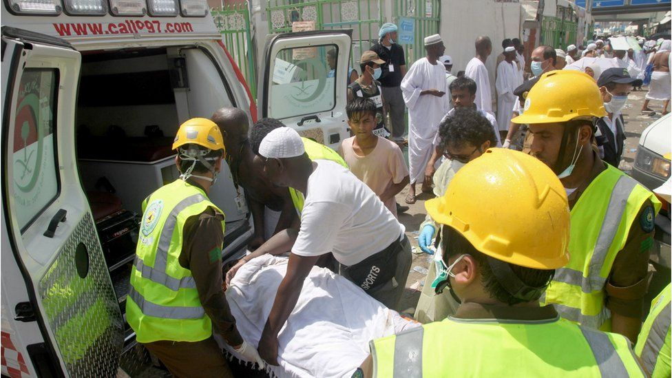 Saudi emergency workers at Hajj pilgrimage load a wounded person into an ambulance
