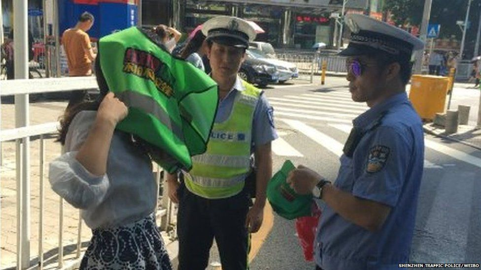 A woman being made to put on a green vest by a police officer