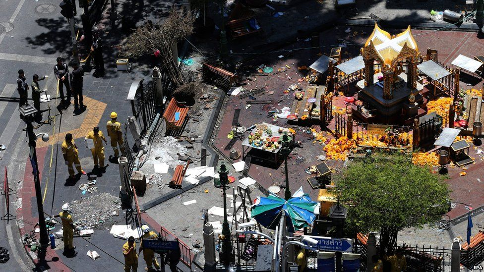 Thai police officers and emergency staff inspect the scene where Monday's bomb was detonated outside Erawan Shrine, central Bangkok, Thailand on Tuesday