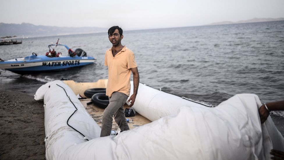 A man stands on a boat abandoned on the shore of Bodrum, southwestern Turkey, early on August 19, 2015.