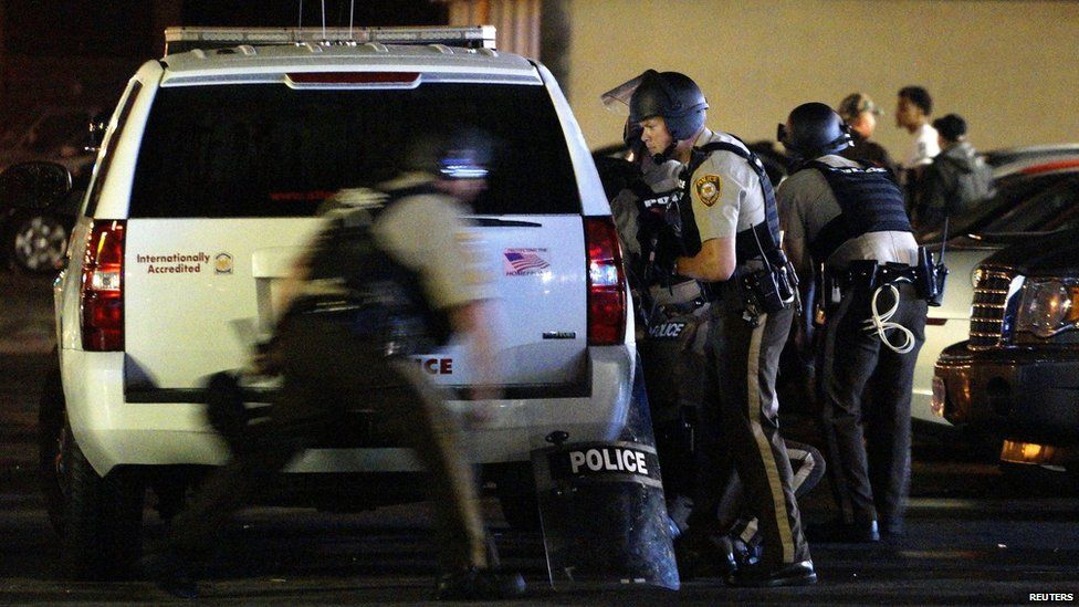 A police officer runs to take cover after shots were fired in a police-officer involved shooting in Ferguson, Missouri August 9, 2015.