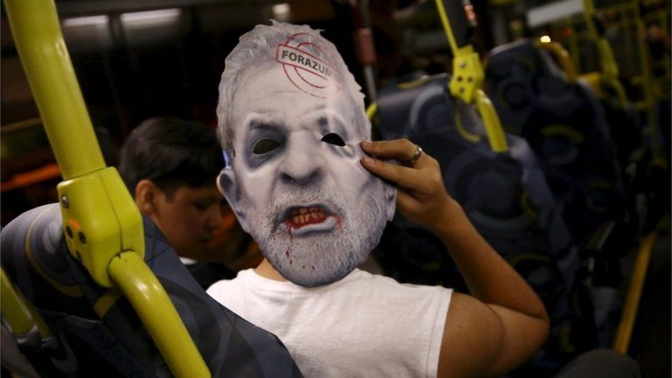 """A demonstrator inside a bus wears a mask depicting Brazil's former president Luiz Inacio Lula da Silva after a protest against Brazil""""s President Dilma Rousseff, which is part of nationwide demonstrations calling for her impeachment, in Sao Paulo, Brazil, on 13 March, 2016"""