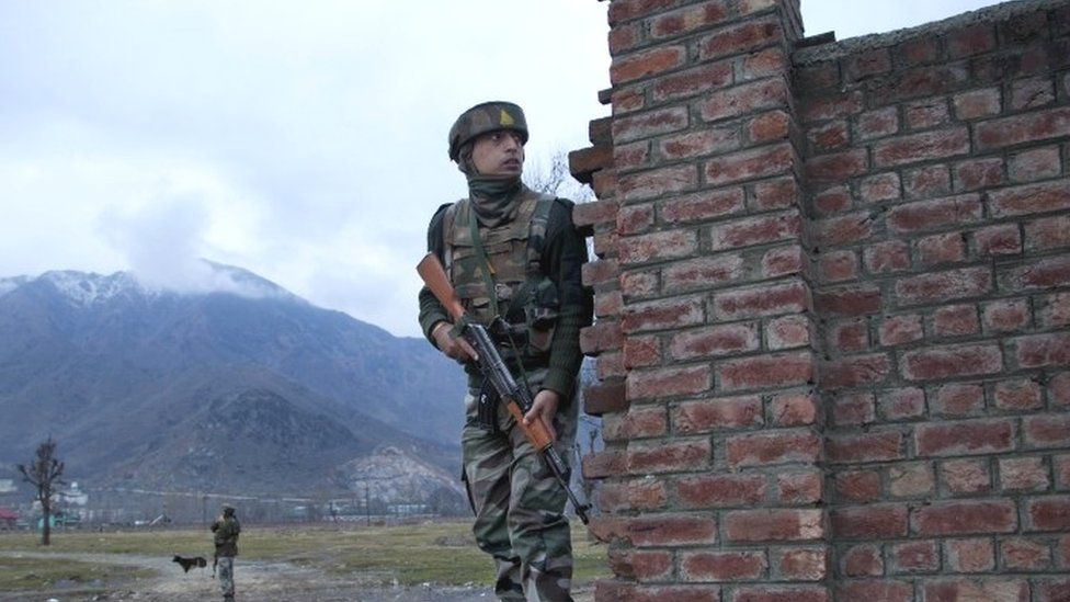 An Indian soldier watches from a distance as he takes position behind a wall near the site of the gun battle on the outskirts of Srinagar (20 February 2016)