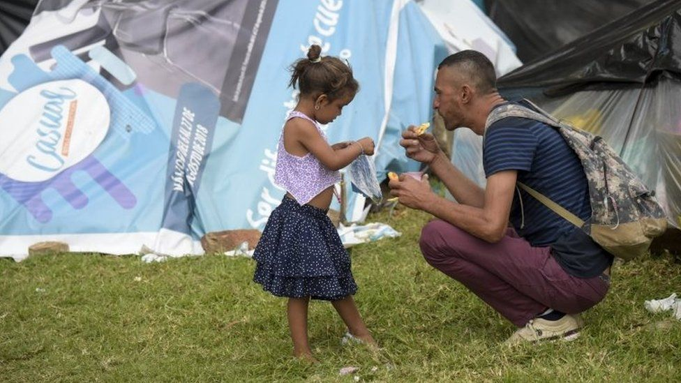 A Venezuelan migrant man and a girl are pictured at an improvised camp near the bus terminal in Bogota on September 11, 201