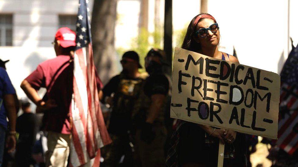 Frau bei Antivax-Protest mit Schild mit der Aufschrift medizinische Freiheit für alle