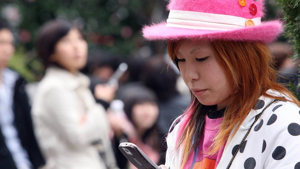 A Japanese woman uses a mobile phone on March 24, 2006 in Tokyo, Japan.